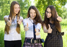 Three student girl with thumbs-up in the park. Three happy student girl with thumbs-up in the park Royalty Free Stock Photo
