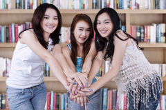 Three student joining hands in library Stock Images