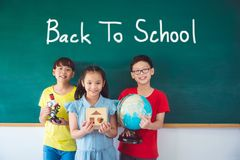 Three student smiling in front of chalkboard Stock Photo