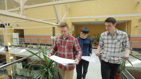 Three student walk with blueprint inside university of art. stock footage