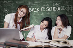 Three students back to school and studying in class Stock Images