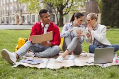 Three students discussing current world events. World events. Three good-looking students feeling involved in discussing current world events together Royalty Free Stock Images