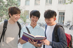 Three students discussing and looking at the book Stock Photo