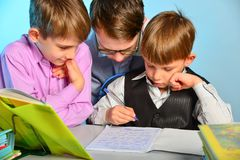 Three students do school lessons together, solve homework tasks.  stock photos