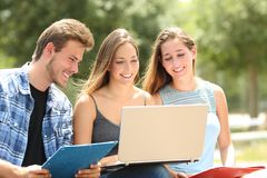 Three students e-learning together in a campus. Three happy students e-learning together sitting on a bench in a campus stock images