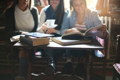 Three students girls teaching in cafe. Focus on foreground. stock photo