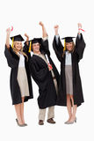 Three students in graduate robe raising their arms Stock Photography