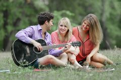 Three students with a guitar sitting on the grass in the city Park.  stock photos