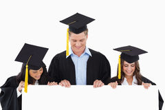 Three students having graduated holding blank sheet and looking Stock Image