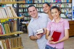 Three students in library. Three happy students in library Royalty Free Stock Photo