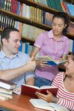 Three students in library. Three happy students in library studing Royalty Free Stock Photography