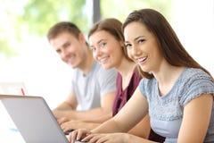 Three students looking at you at classroom. Portrait of three happy students looking at you at classroom Royalty Free Stock Photography