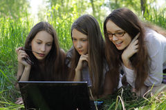 Three students  in the park with notebook Royalty Free Stock Images