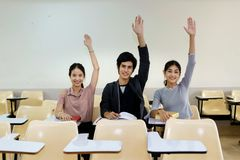 Three students raised their hands together in the classroom. Stock Photos