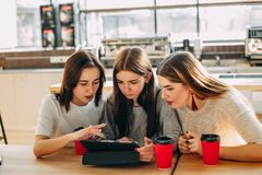 Students read and discuss content at tablet pc Stock Image