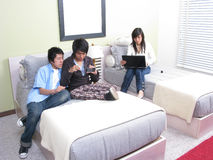 Three students relaxing on the bed with laptop Royalty Free Stock Images
