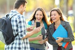 Three students sharing phone content in a park royalty free stock photos