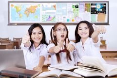 Three students showing thumbs up. Concept of Back to School. Group of three female high school students showing thumbs up in the classroom with books on the Stock Photos
