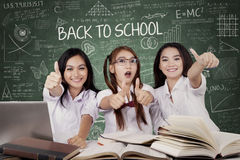Three students shows thumbs up. Concept of Back to School. Group of three beautiful high school student showing thumbs up with books on the table and a text of Royalty Free Stock Photography