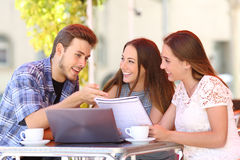 Three students studying and learning in a coffee shop. With a laptop and notes Royalty Free Stock Images