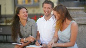 Three students studying outdoors and laughing together during warm sunny day in the city. Two girls and one boy with stock footage