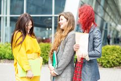 Three students talk and laugh at the university. Education concept, friendship and group of people.  stock photos