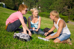 Three students talking in the park Stock Images