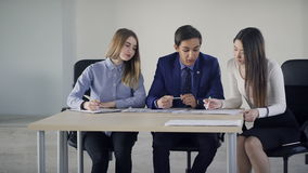 Three students talking sitting on table in classroom. Young man dressed in stylish blue suit with black tie and two cute women seats next to him are preparing stock video footage