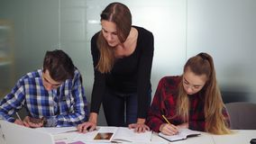 Three students working on their homework sitting together at the table while one girl is dictating and two other. Students are writing. Slowmotion shot stock video footage