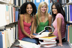 Three students working in university library. Three female students sitting on floor of library surrounded by books stock photo