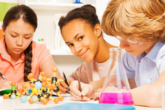 Three students writing chemical formula at class. Three multi ethnic students writing chemical formula sitting at the desk in science class Royalty Free Stock Photos