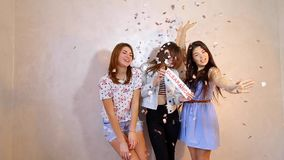 Three stylish female friends posing with sign clearence and calling for shopping, stand in room against background of stock footage
