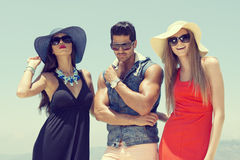 Three stylish friends standing by the pool Royalty Free Stock Images