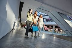 Three stylish girls dressed in nice casual clothes walk with lots of shopping bags in the modern mall. Shopping time stock photo