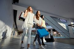 Three stylish girls dressed in nice casual clothes walk with lots of shopping bags in the modern mall. Shopping time stock photos