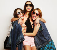 Three stylish sexy hipster girls best friends. Fashion portrait of three stylish sexy hipster girls best friends, over gray background. Happy time for fun Stock Photos