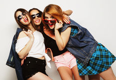 Three stylish sexy hipster girls best friends. Fashion portrait of three stylish sexy hipster girls best friends, over gray background. Happy time for fun Royalty Free Stock Photography