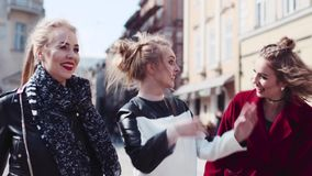 Three stylish woman gathered together and walking down the street laughing and communicating. Stylish outlook, beauty. Blogger. Sunny weather. True friendships stock video footage