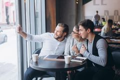 Three successful business people taking Selfie. Three successful business people taking a happy Selfie in the cafe Royalty Free Stock Photo