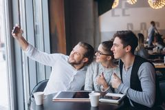 Three successful business people taking Selfie. Three successful business people taking a happy Selfie in the cafe Stock Image