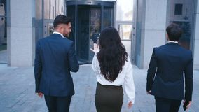 Three Successful Business People: Two handsome Men and beautiful Woman with Confident Gait Walk in the Office Building stock footage