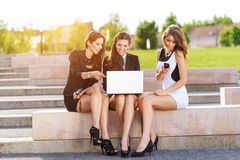 Three Successful businesswomen in the city on a bench discussed Royalty Free Stock Photo