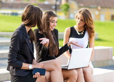 Three Successful businesswomen in the city on a bench discussed Royalty Free Stock Images