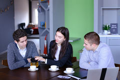 Three successful colleagues, girl and two guys sum up work in in Stock Photography