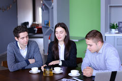 Three successful colleagues, girl and two guys sum up work in in Royalty Free Stock Photos
