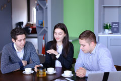 Three successful colleagues, girl and two guys sum up work in in Royalty Free Stock Photography
