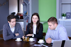 Three successful colleagues, girl and two guys sum up work in in Stock Photos