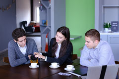Three successful colleagues, girl and two guys sum up work in in Stock Images