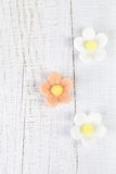 Three Sugar Blossom Flowers On White Old Table Royalty Free Stock Photography