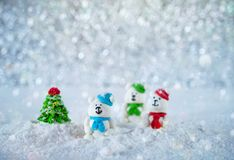 Three sugar candy bears in the snow on bokeh background with copy space for season greeting Merry Christmas or Happy New Year Royalty Free Stock Photo